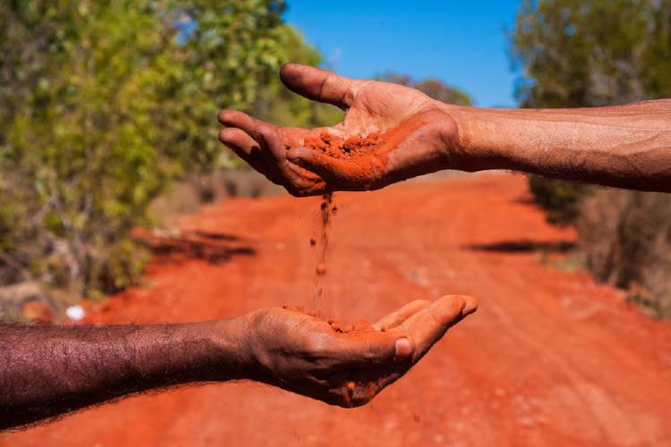 Una mano deja caer tierra roja sobre otra