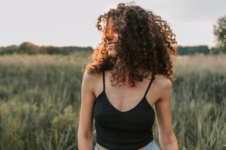 Mujer sonriente con cabello rizado en la naturaleza