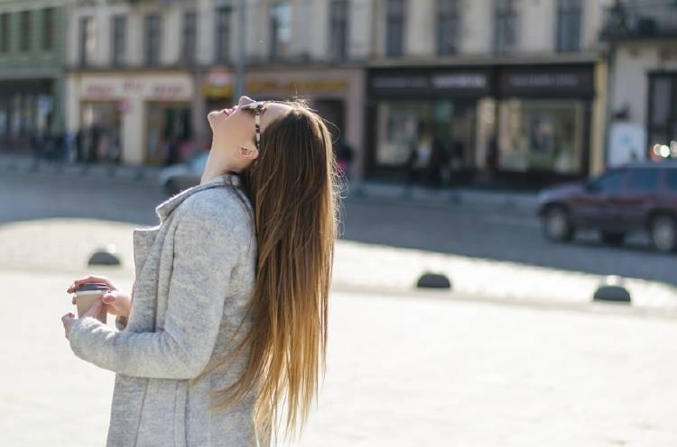 mujer con cabello liso en plaza con café en la mano