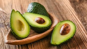 Aguate picado por la mitad con semilla y sin semilla dentro de un plato de madera sobre una mesa de madera