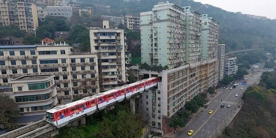 Este tren chino pasa por en medio de una zona urbana de una manera muy particu..