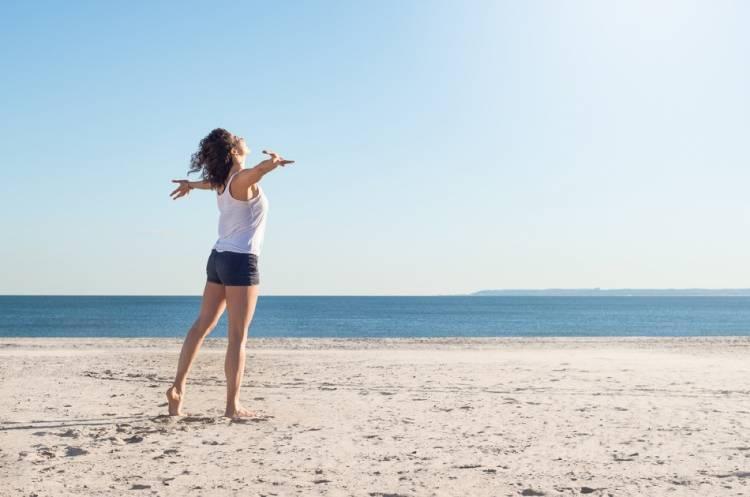 Mujer en la playa en contacto con la naturaleza