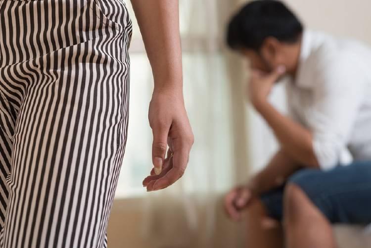 Una mujer se aleja de un hombre con expresión de tristeza