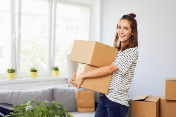 mujer sostiene cajas de carton para hacer la limpieza de su hogar