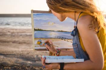 joven pinta un cuadro en la playa