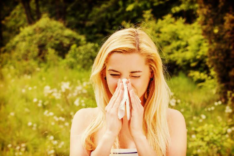 Una mujer con alergia se suena la nariz