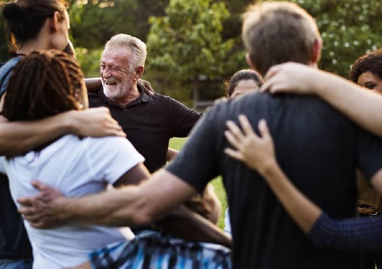 personas abrazadas en circulo con amigos felices