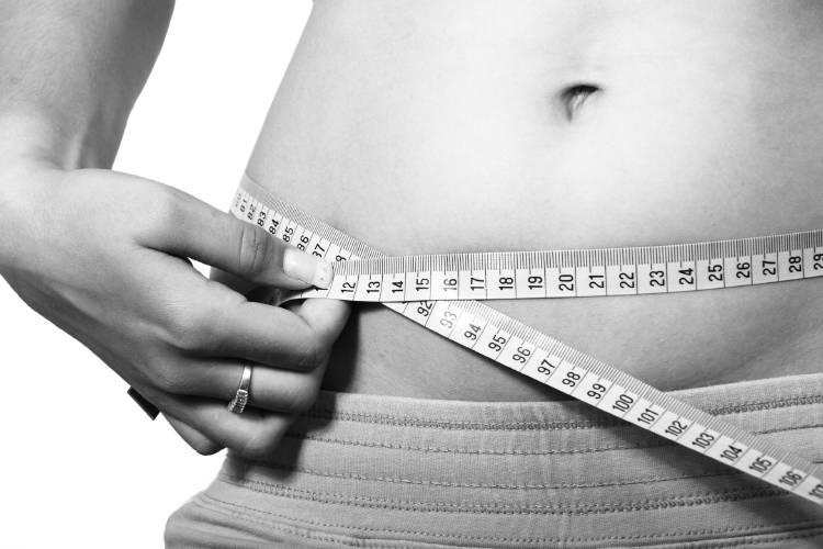Una mujer mide su abdomen