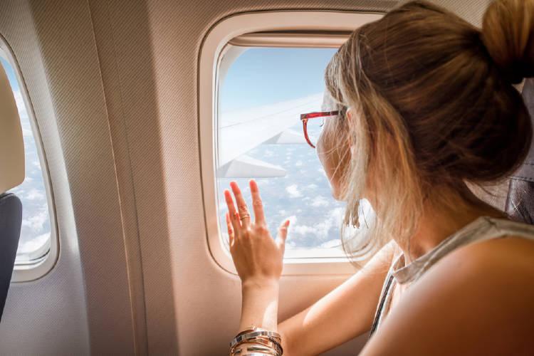 Una mujer mira por la ventanilla de un avión