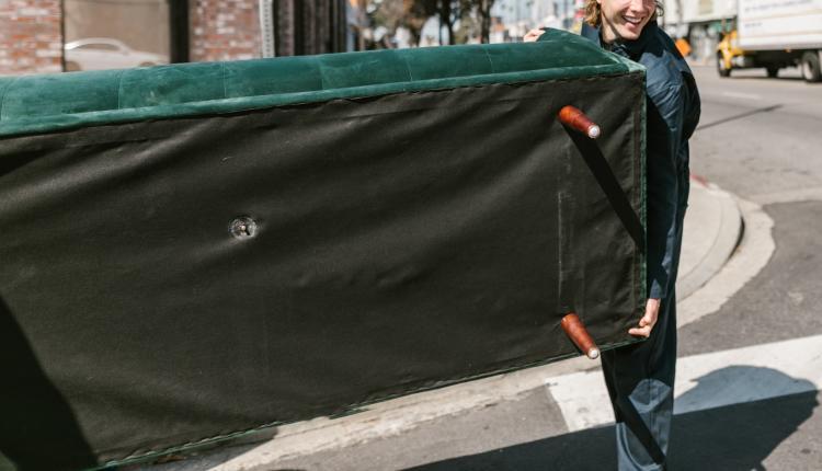 Hombre levantando sofa en la calle