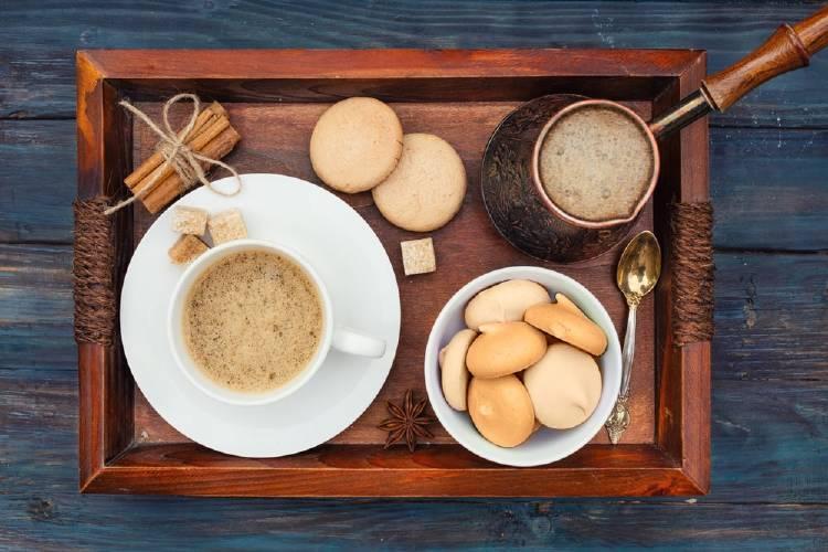 bandeja de madera con ramas de canelas amarradas con un lazo, un plato con una taza de café con leche y terrones de azúcar, un bowl con galletas, una cuchara para postres y una jarra de mango largo con cafe con leche. Sobre una mesa de madera azul