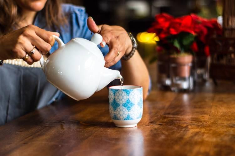mujer sirviendose una taza de té sentada en una mesa de madera