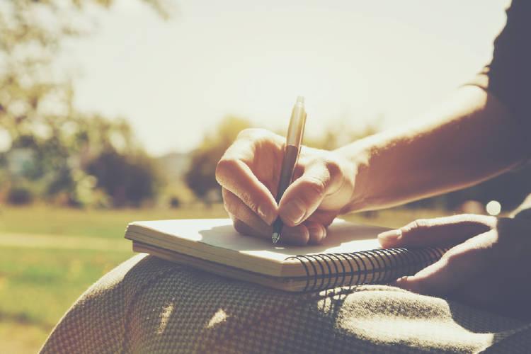 Una persona escribe en un cuaderno en un parque