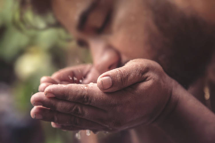 Un hombre bebe agua de sus manos