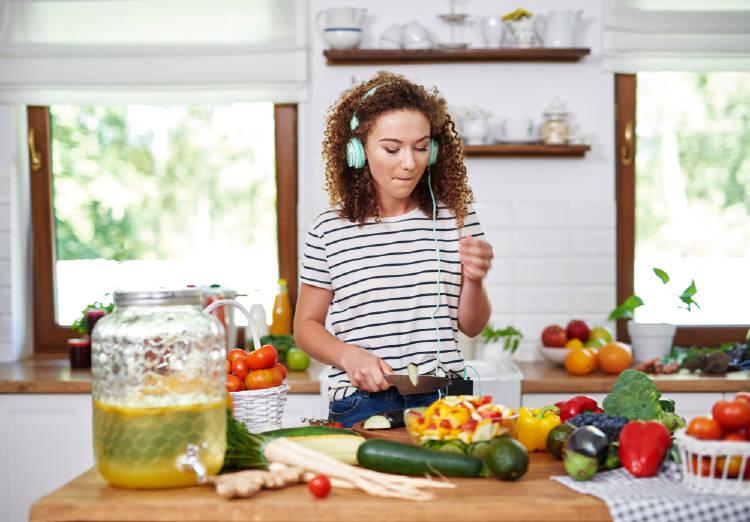 Una mujer cocina mientras escucha musica