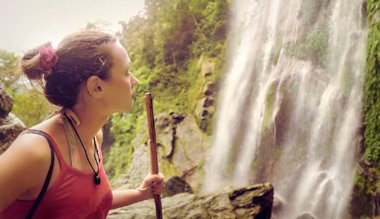 mochilera en una cascada trekking ecoturiso