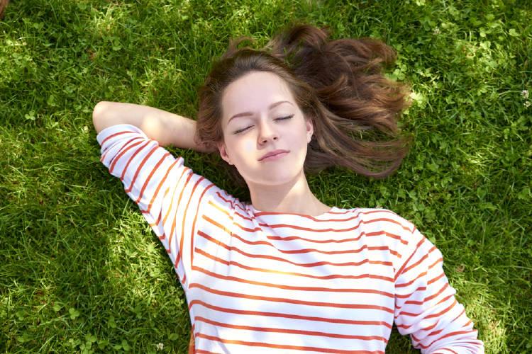 Una mujer recostada sobre el césped con los ojos cerrados