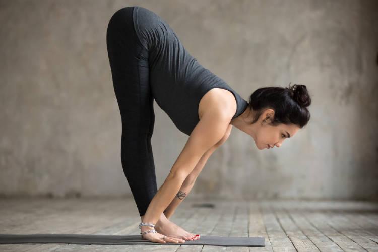 Una mujer haciendo la postura de yoga de la media pinza