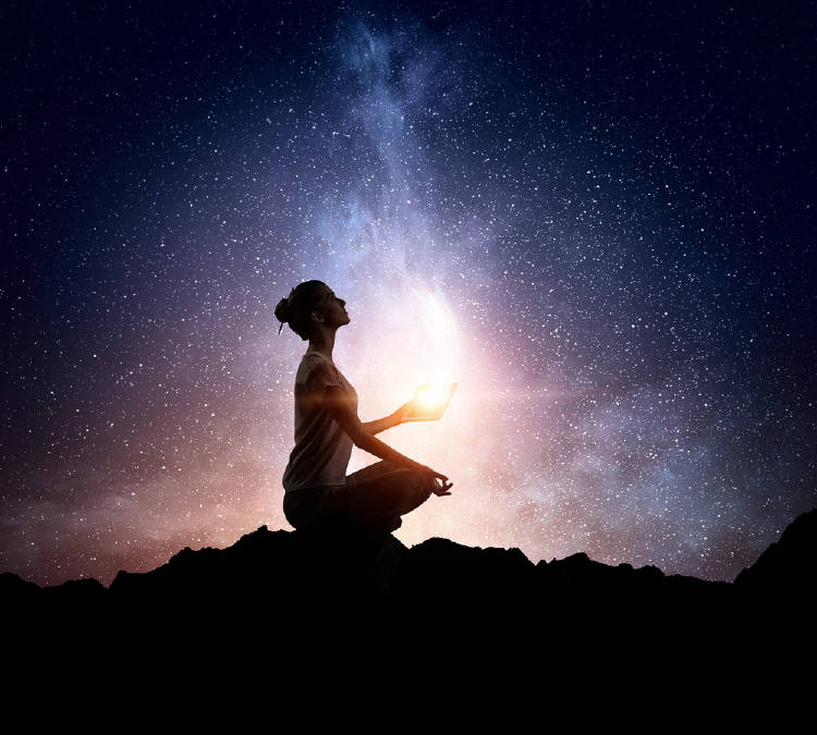 silueta de mujer medita en el cosmos