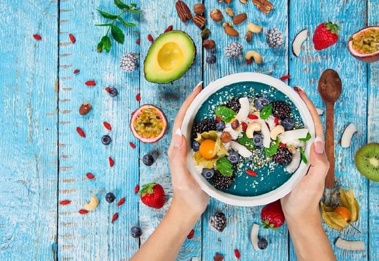 Una persona toma un recipiente lleno de frutas y verduras saludables