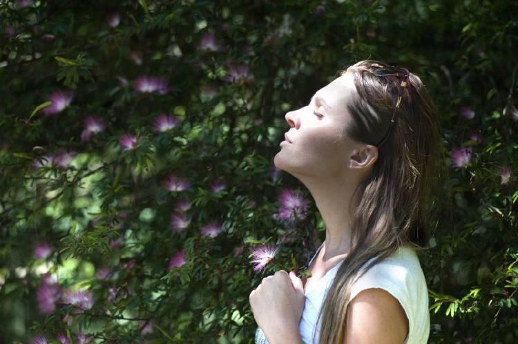 Una mujer de frente al sol con flores y plantas de fondo