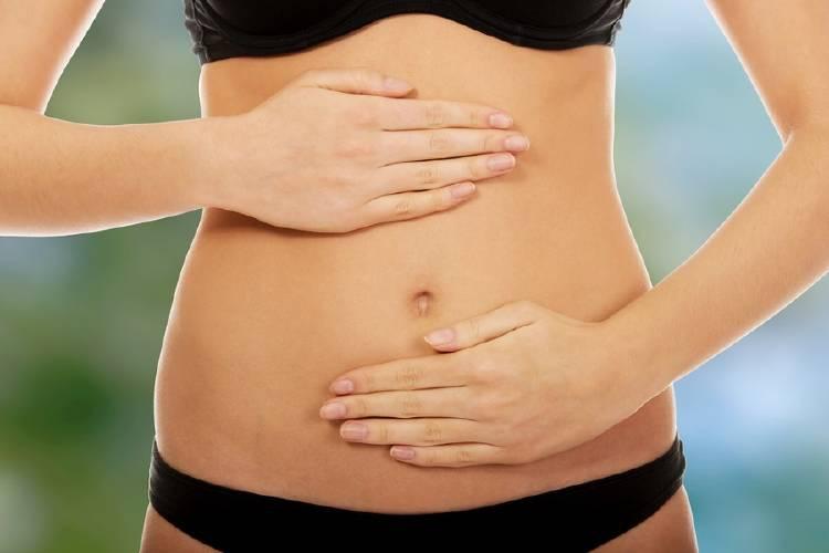 mujer se da automasaje en el abdomen