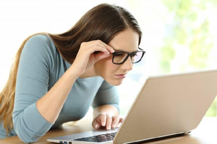 Una mujer con anteojos frente a una computadora