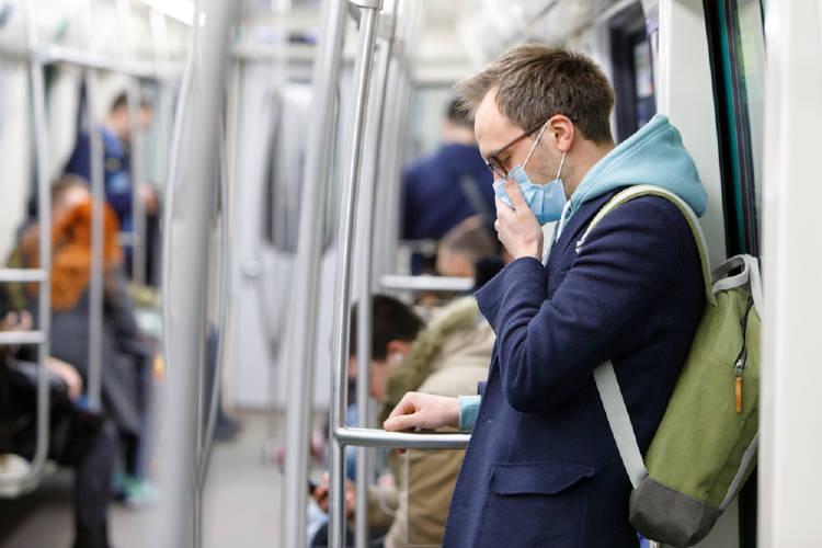 hombre en el subte con barbijo para evitar contagio