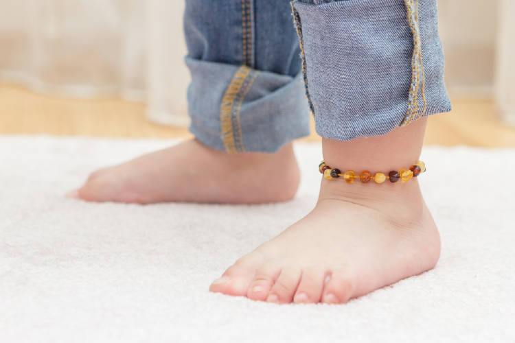Los pies de un bebé con una tobillera de ambar