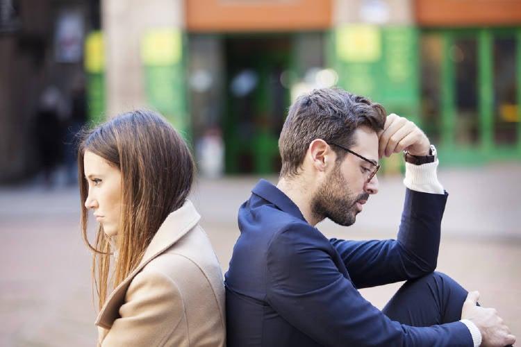 Un hombre y una mujer sentados de espaldas