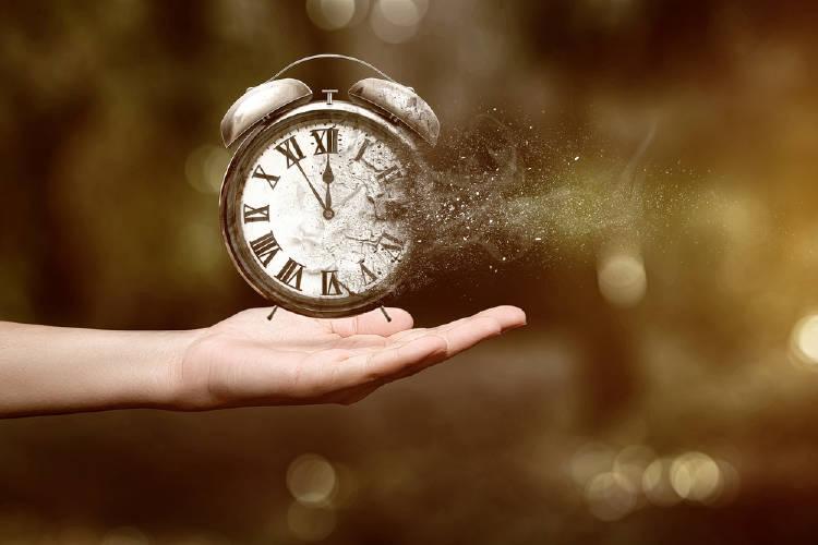 Una mano sostiene un reloj que se desintegra