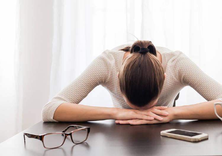 Una mujer estresada con la cabeza apoyada sobre la mesa
