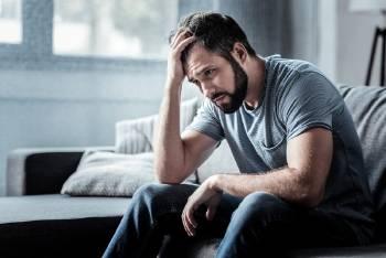 Un hombre triste sentado en un sillón