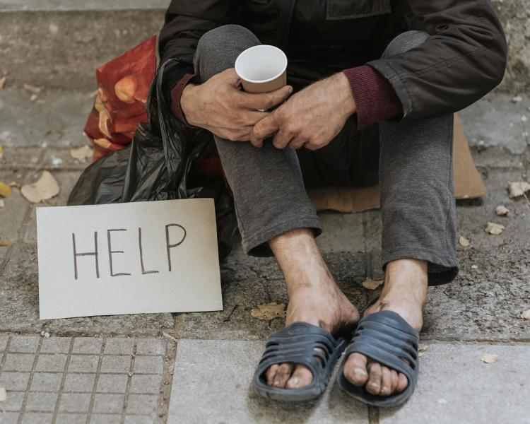 front-view-of-homeless-man-outdoors-with-help-sign-and-cup