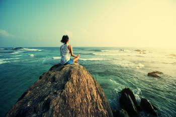 Mujer meditando frente al océano.