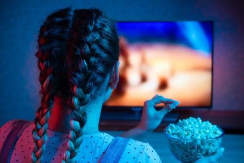 Una niña come pochoclo frente a la tele