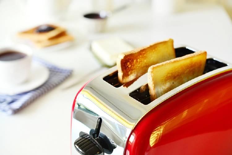 Un tostador con tostadas listas en una mesa con café