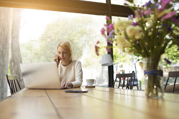 Una mujer trabaja en una mesa con un florero