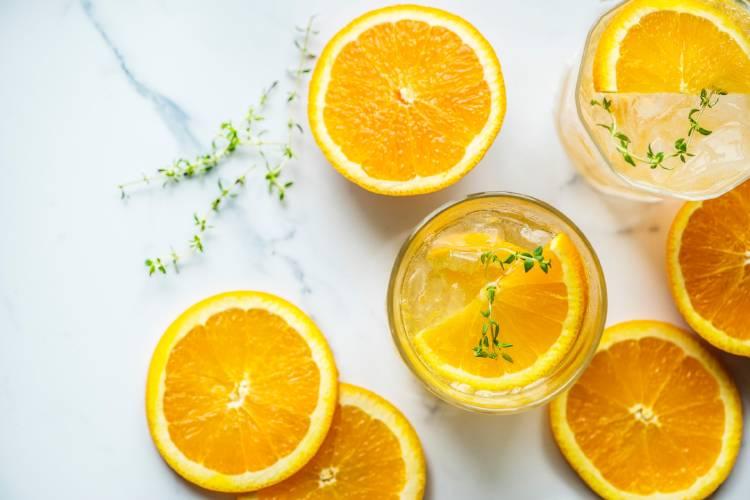 Naranjas cortadas al medio y dentro de un vaso