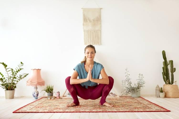 Una mujer practicando yoga en la postura Malasana