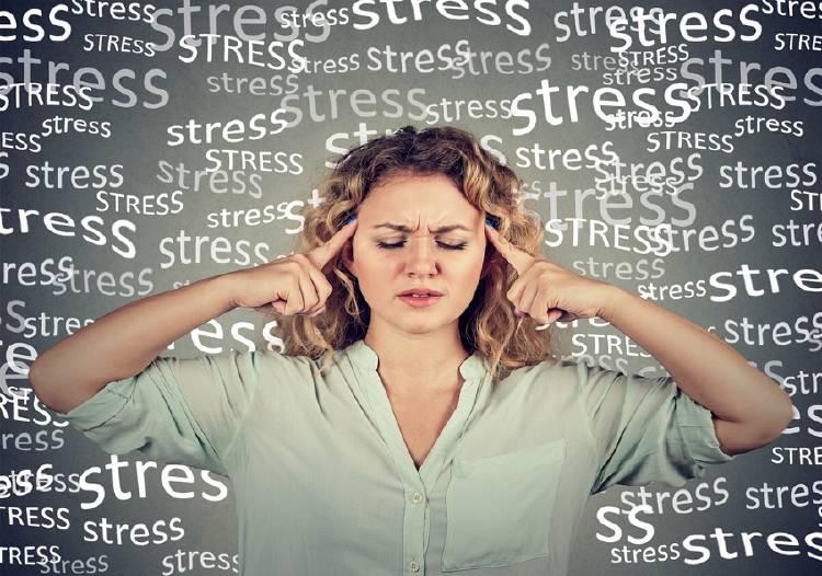 mujer se sostiene la cabeza por el estrés