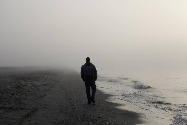 hombre camina en playa con niebla