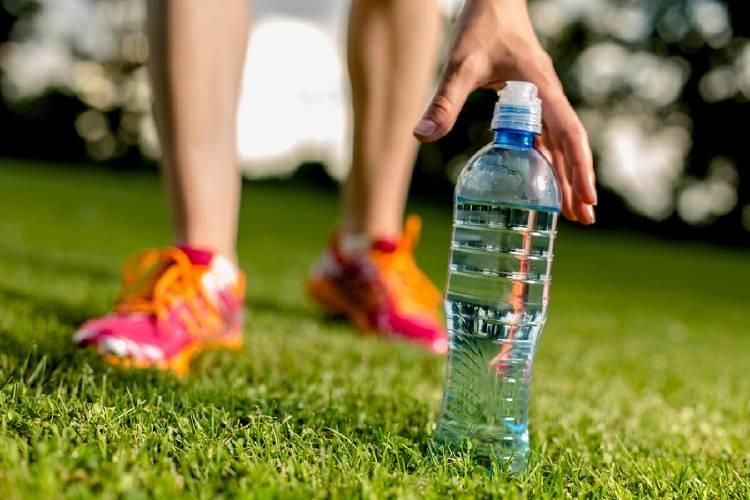 mujer recoge botella de agua luego de hacer ejercicio