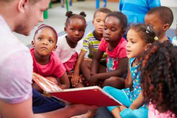 hombre voluntario enseña a leer a niños que viven en comunidades desfavorecidas