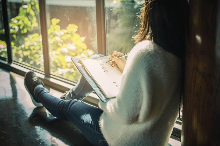 mujer escribe en su cuaderno mirando hacia la ventana