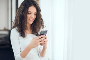 mujer sonriente escribe en su celular