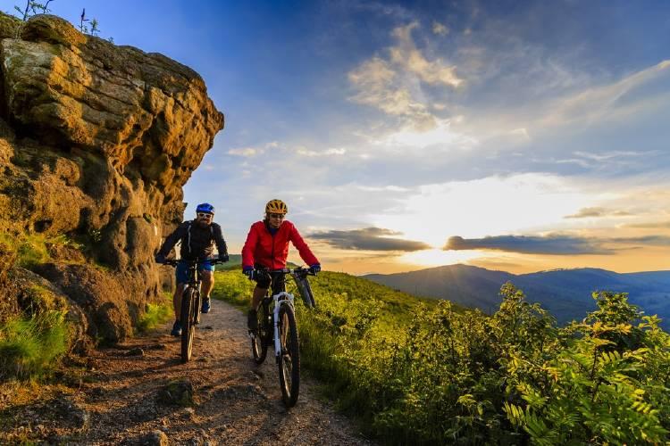 dos personas en mountain bike en la montaña al atarceder ecorutismo