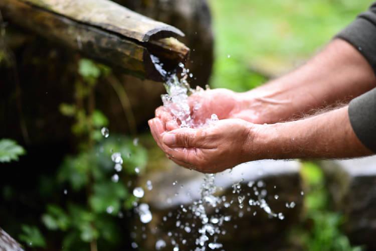 Un hombre moja sus manos en agua potable