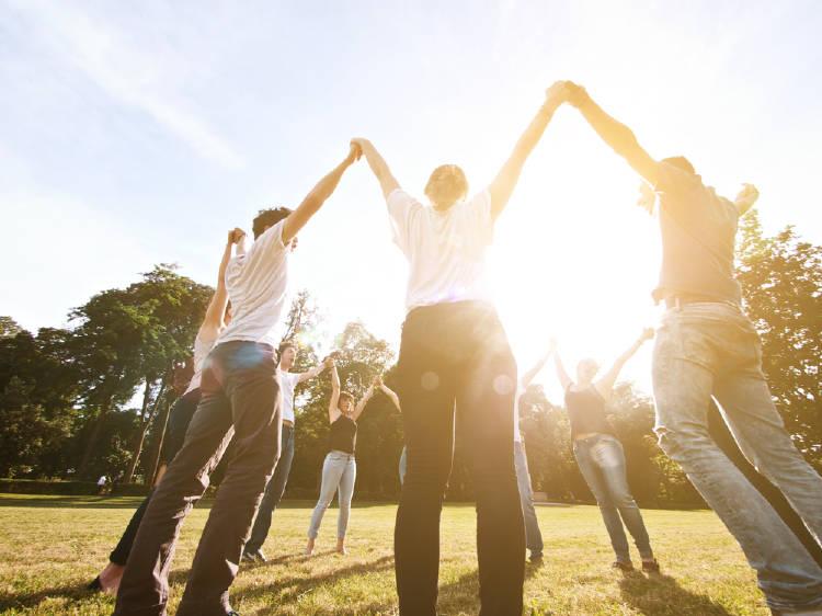 un grupo de personas baila en circulo al aire libre