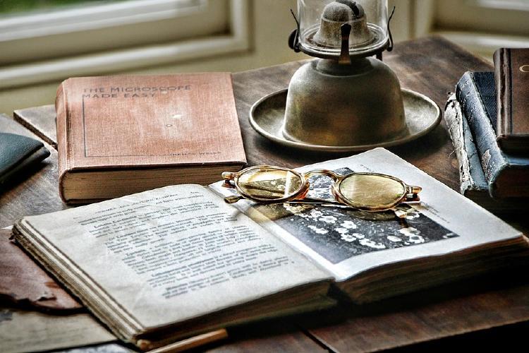 Libros anteojos y lámpara